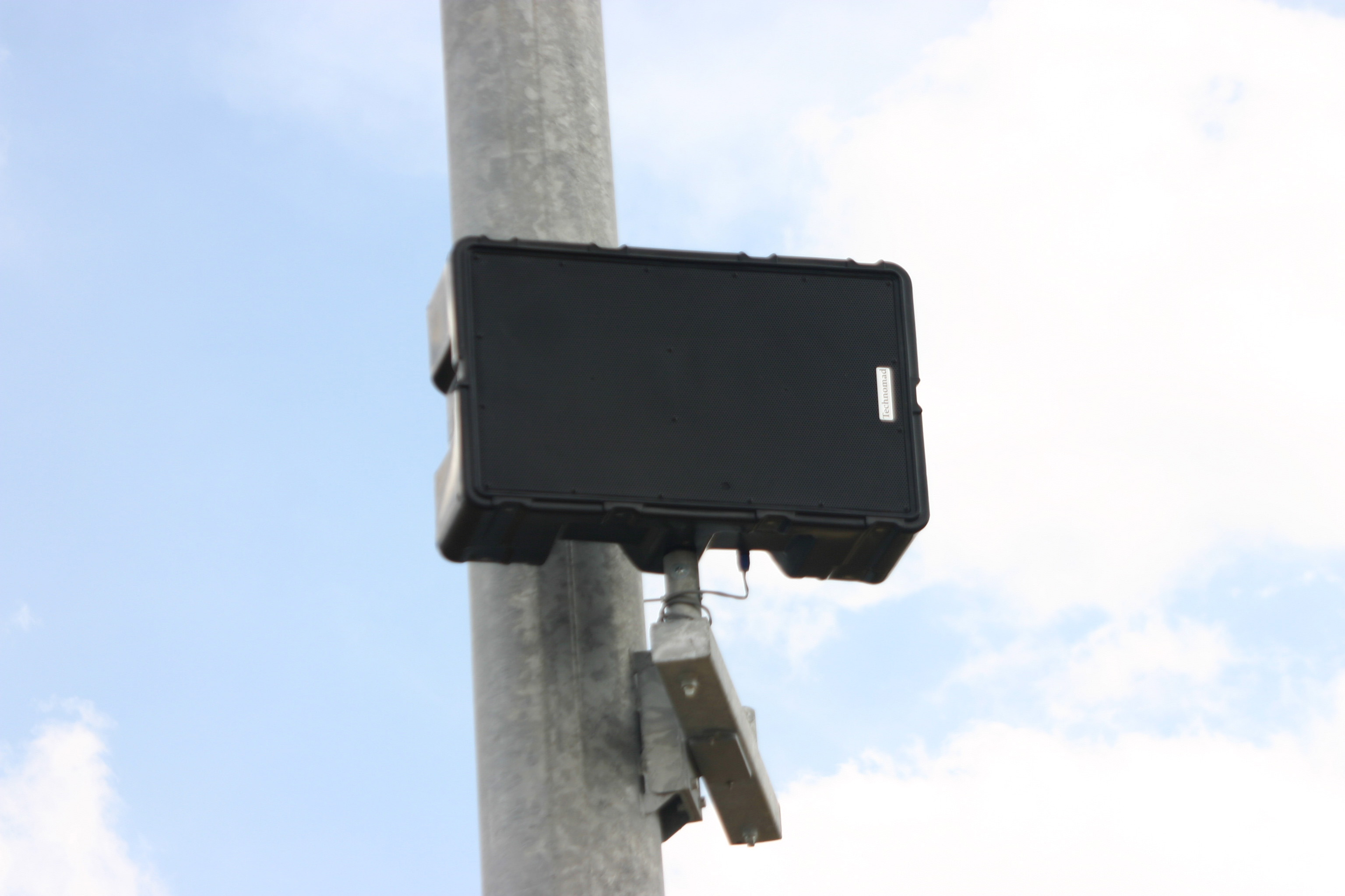 A Technomad Berlin loudspeaker installed on a light pole outdoors and unprotected from the elements