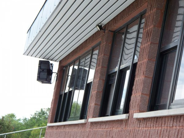 Noho waterproof speakers on the press box façade following masonry work to smooth the textured brick surface for the mounts